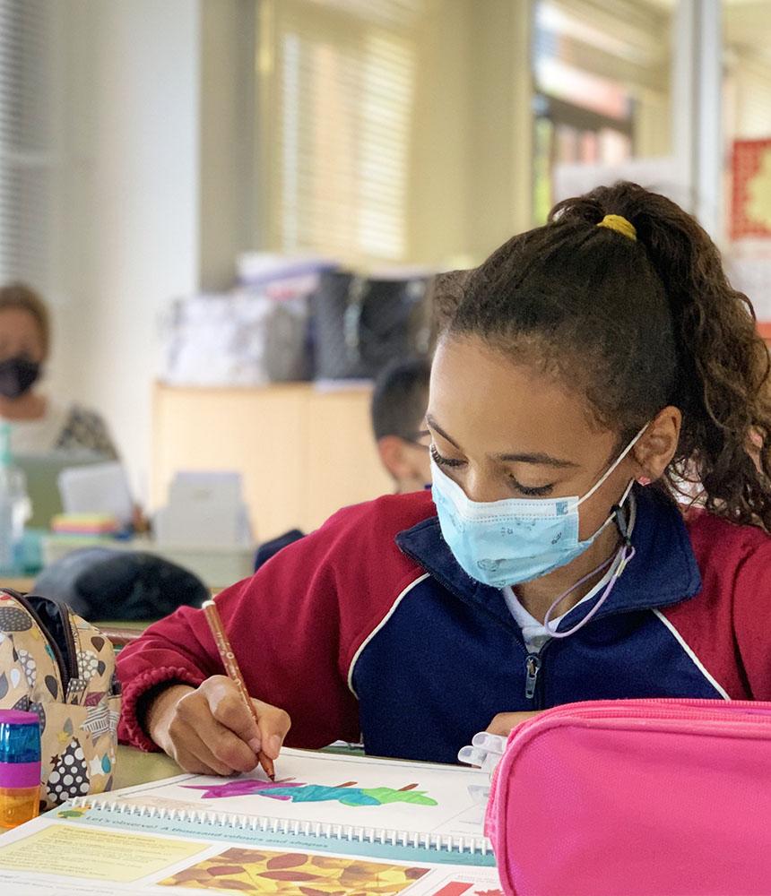 niña pintando en el aula del colegio