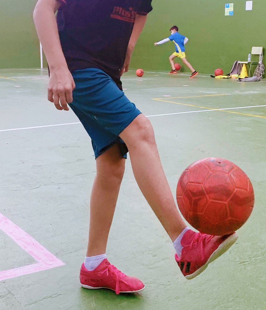 niño jugando con un balón en el patio del colegio